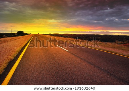 Long road through African country side at sunrise - stock photo
