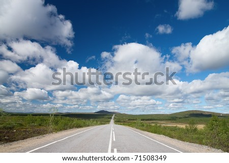 Long road to green hills.  Kola Peninsula. - stock photo