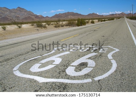 long road with a Route 66 sign painted on it - stock photo