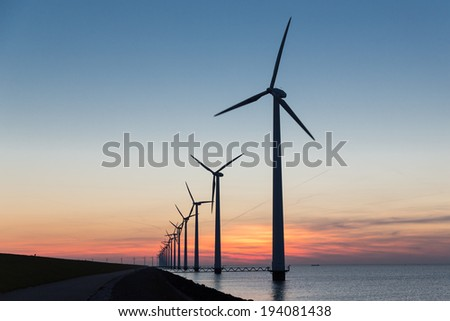 Long row Dutch offshore wind turbines at beautiful sunset - stock photo