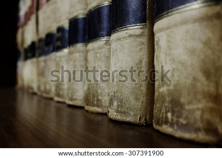 Long row of old leather law books on a shelf - stock photo