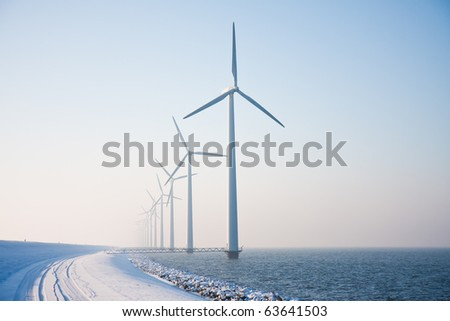 Long row of snowy windmills standing in Dutch sea disappearing in winter haze - stock photo