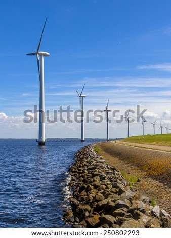 Long Row of wind turbines in the sea along a dike in the Netherlands