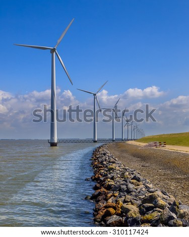 Long row of wind turbines positioned in water offshore along the coast