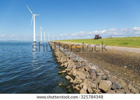 Long row off shore wind turbines along the Dutch coast with a tractor mowing the grass of the dike - stock photo