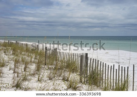 Long sand fence runs along white sandy beach and dunes in Florida. Fence lessens effects of erosion from wind and water in the dunes.