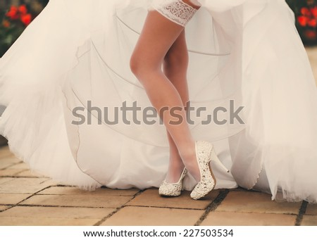 Long sexy legs wonderful bride posing on the pavement. Wedding creamy dress. Fashion shoes for bride and wedding.  - stock photo