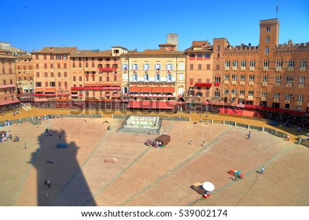 Long shadow of Torre del Mangia's across Piazza del Campo before the Palio horse race, Siena, region of Tuscany, Italy