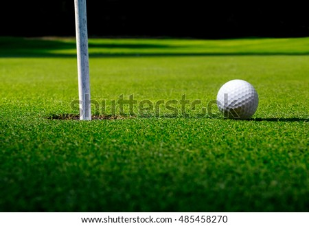 Long shadows on golf field with a ball, hole and sunlight. Sport-club landscape for leisure and playing with a ball on green grass. Sport background - lawn and elements of sport games.