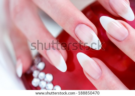 Long, sharip nails adter manicure with red object with classy diamonds - stock photo