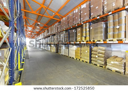 Long shelves with goods in distribution warehouse