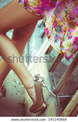 long slim woman legs in high heel shoes lean on old door with glass outdoor shot retro colors - stock photo