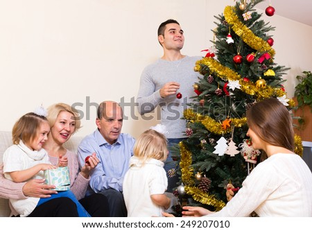 Long smiling family with grand children decorating New Year tree - stock photo