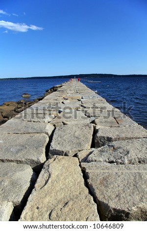 Long stone path made from large rock boulders leading to a lighthouse on the water on sunny summer day. / Stone Path