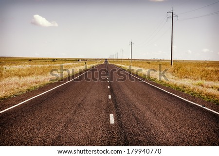 Long straight road in the Australian outback with power poles beside it, with an instagram filter. - stock photo