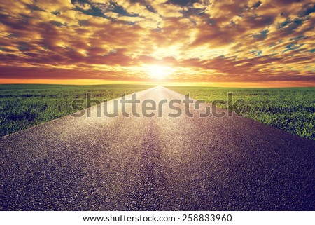 Long straight road, way towards sun. Sunset sky, travel, transport, destination concepts. - stock photo