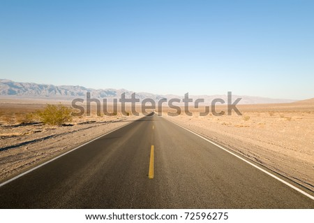 Long straight tarmac road heading into the desert of Death Valley