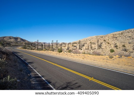 Long stretch of unbroken abandoned highway in empty desert. - stock photo