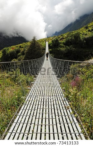 Long suspension foot bridge with silhouette of walking woman, bridge over deep valley in mountains, Himalaya, Nepal - stock photo