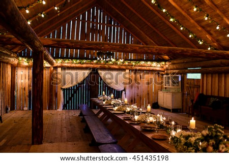 Long table stands in the wooden storage decorated for a wedding - stock photo
