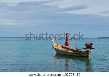 long tail boat and red umbrella.