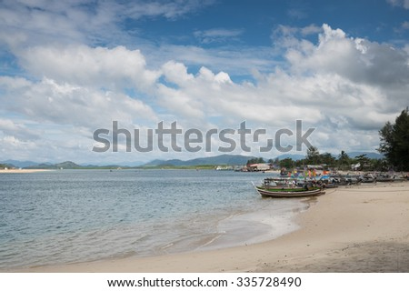 Long-tail boat at tropical beach with blue sky