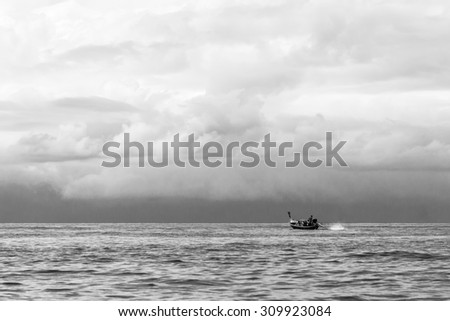 Long tail boat on the sea with a stormy weather at Krabi, Thailand. Black and White tone.