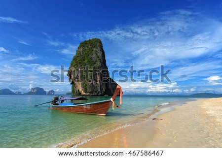 Long tail boat on tropical beach with limestone rock / Krabi / Thailand