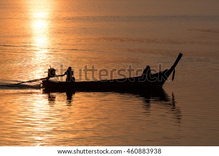 long tail boat silhouette on sunrise