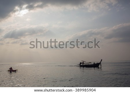 Long-tail boat under beautiful sun rays at sunset in gorgeous Maya bay, Phi-Phi, Thailand. Image with selective focus and toning - stock photo