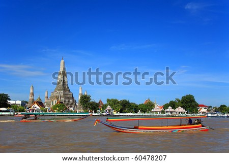 Long tail motor boat cruise in front of Wat Arun in Chaopraya river - stock photo