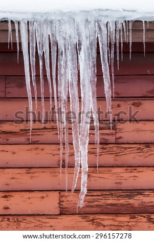 Long thick icicle  hang down of  the roof of a red barn in winter. - stock photo