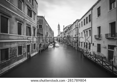 Long time exposure of canal in Venice (Venezia) with old buildings, boats and the leaning belfry tower of San Giorgio dei Greci, Italy, Europe, vintage black and white style - stock photo