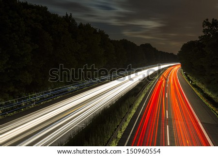 long time exposure on a highway with car light trails and cloudy sky - stock photo