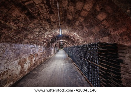 Long underground brick tunnel in the wine cellar - stock photo