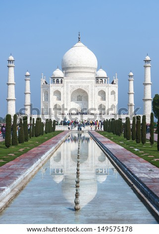Long view on Taj Mahal mausoleum with reflection in canal at India's Agra. Massive monument with four minarets against blue sky. - stock photo