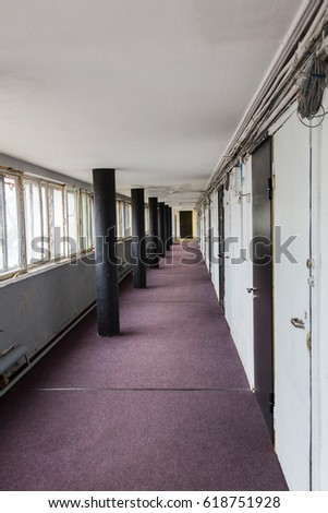 Long walkway between buildings with carpet and doors