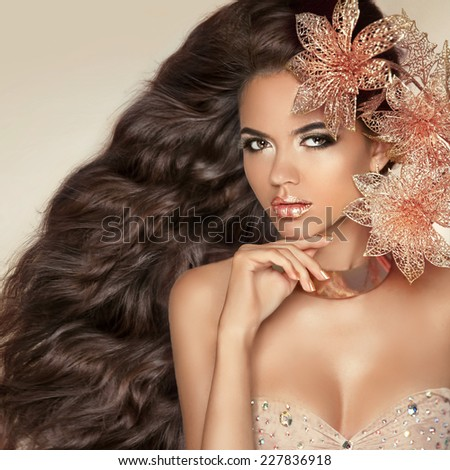Long wavy hair. Beautiful Attractive brunette Girl With Flowers. Healthy hairstyle. Beauty Model Woman Face. Professional Make-up. Makeup.  - stock photo