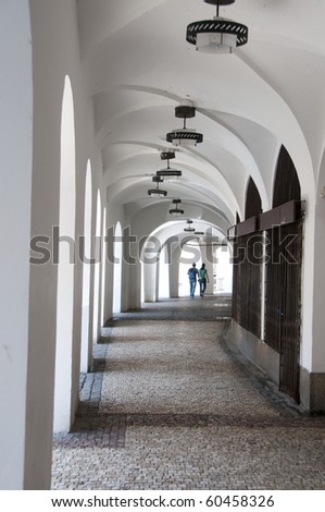 Long, white arched, arcade with light at the end and young couple holding hands, walking away at the far end