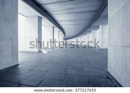 Long wide corridor of the building with columns at summer day time. - stock photo