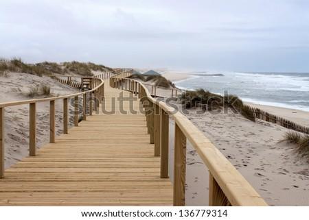 Long wooden boardwalk along the Atlantic Ocean in Praia Barra, Aveiro, Portugal - stock photo