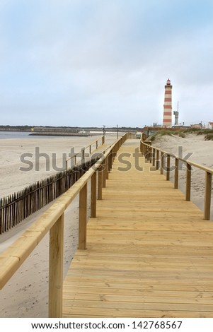 Long wooden boardwalk along the Atlantic Ocean in Praia Barra, Aveiro, Portugal with lighthouse in the distance