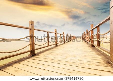Long wooden bridge  in beautiful island beach sunset - stock photo