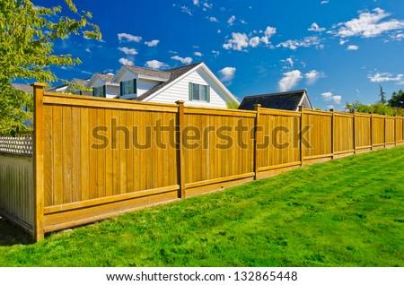 Long wooden cedar fence. - stock photo