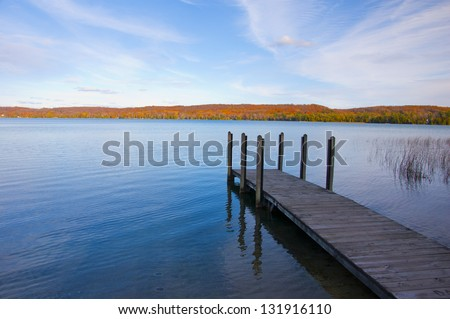 Long wooden dock leading into water, with autumn colors in distance