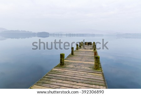 Long wooden jetty on a misty spring morning at Windermere in the Lake District, UK. - stock photo