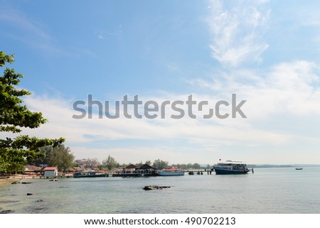 Long wooden jetty with charter boat in calm shallow water tethered outdoor in the tropical ocean at Sihanoukville, Cambodia