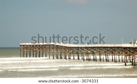 Long wooden pier into ocean with overcast sky
