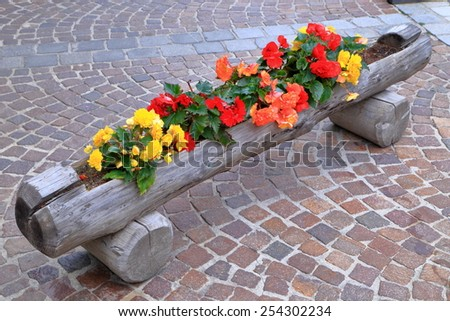 Long wooden pot made of a log on the sidewalk - stock photo