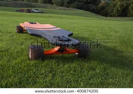 longboard park shadow. Black and orange longboard on a green lawn grass